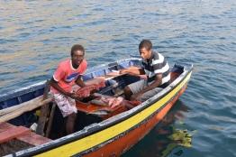 Killar som säljer fisk vid båten